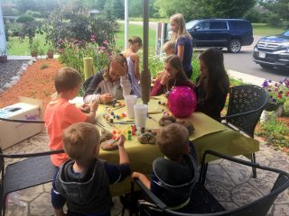 Winchester Library kids painting rocks to hide in the Memorial Garden outside the Library.